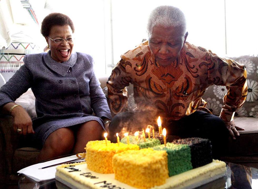 28. Нельсон Мандела, бывший президент Южной Африки, задувает свечи на торте на свой 91-ый день рождения в Йоханнесбурге 18 июля; рядом – супруга Нельсона Граса Машел. (Debbie Yazbek/AFP /Getty Images)