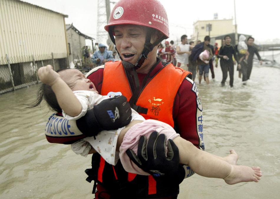 29. Спасатель выносит ребенка из затопленного района после тайфуна Моракот в южном Тайване 9 августа. Шторм принес с собой более 203,20 см осадков в некоторых южных странах, это стало худшим наводнением в этом районе за последние полвека. (AP)