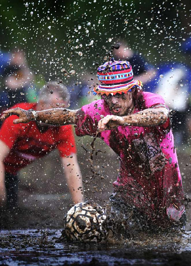 30. Футболист пытается достать мяч из грязи во время мирового чемпионата по футболу в грязи в Хюрюнсалми, Финляндия, 17 июля. (Vesa Moilanen/AFP /Getty Images)