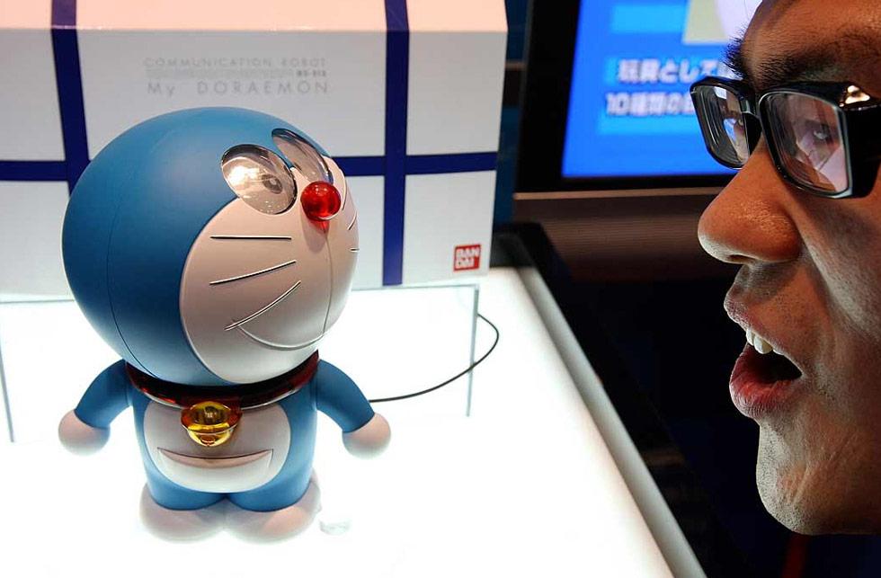 31. Человек общается с японской игрушкой Дораэмон на международной выставке игрушек в Токио 16 июля. Игрушка умеет говорить 130 фраз и имеет фонарик, звук, оптические и температурные сенсоры. (Junko Kimura/Getty Images)