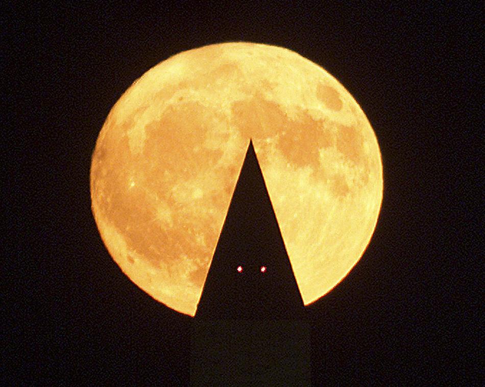 3) Оранжевая луна урожая поднимается за Вашингтонским Монументом в середине октября в Вашингтоне, округ Колумбия. Луна Урожая – это полная луна, появляющаяся в день осеннего равноденствия. Каждые два года из трех луна Урожая восходит в сентябре, но иногда она появляется и в октябре. В пик сезона урожая фермеры могут работать поздно ночью под светом этой луны. (Mark Wilson, Newsmakers)