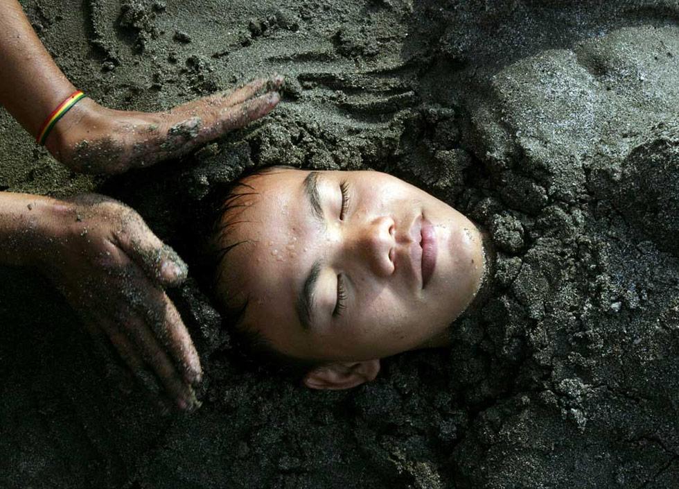 40. Мальчика закопали в песок в Джакарте, Индонезия, где дети со своими семьями наслаждаются последним днем школьных каникул 12 июля. (Arif Ariadi/AFP /Getty Images)