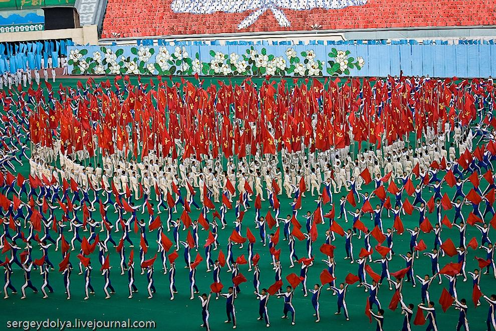 40) Костюмы гимнастов и флаги получаются красивые фигуры на поле.