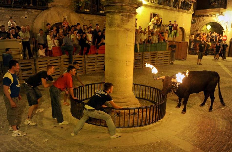 4. Люди убегают от быка с факелами на рогах во время Фиесты Дель Торо Эмбалао в Кретасе, Испания, 15 августа. (Samuel Aranda, Getty Images)