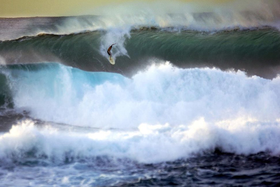 4. Каждую зиму на скалистый северный берег Оаху накатывают самые большие волны на планете. Огромные волны совершают свое путешествие по северному Тихому океану, чтобы разбиться о рифы и береговую линию. Для многих жителей острова это значит только одно: началась пора серфинга! На этом снимке: серфер на гребне одной из крупнейших волн, направляющихся к пляжу Сансет-Бич.