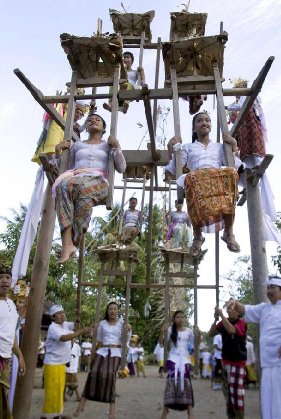 1) Женщины катаются на традиционном чертовом колесе во время церемонии в Теганане, Индонезия, 11 июля. (Firdia Lisnawati/AP)