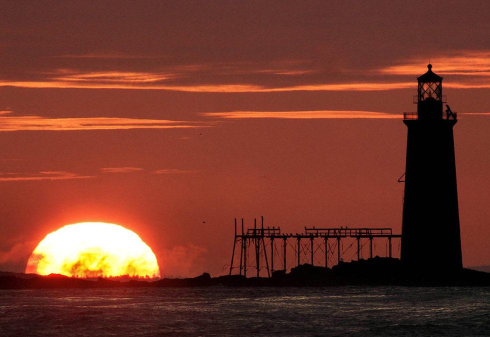 7)  После долгого периода ужасной погоды солнце вернулось в штат Мэн, восходя к востоку от маяка Рэм Айлэнд в устье гавани Портланда 9 июля. Теплая погода станет для жителей этого региона настоящим облегчением, ведь, что с конца мая здесь выпало более 13 дюймов осадков. (Robert F. Bukaty/AP)