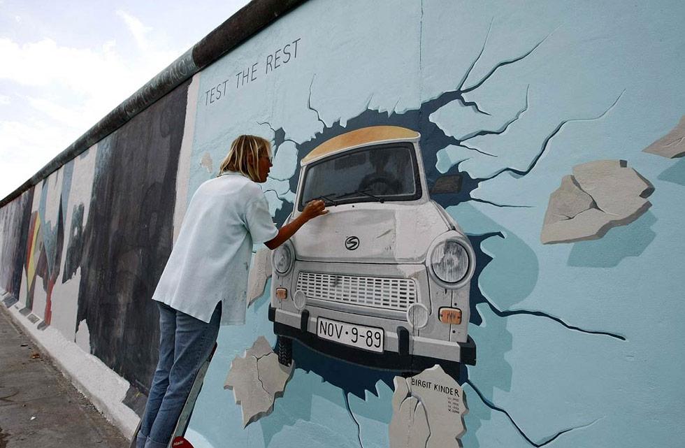 9) Биргит Киндер работает над граффити изображающей неметкий автомобиль «Трабант», нарисованный на самой крупной уцелевшей части бывшей Берлинской стены в Берлине 8 июля. Стену разрисовывали 118 художников из 21 страны в 1990 году, но с тех пор ее повредила плохая погода, выхлопные газы, хулиганы и падкие на сувениры туристы. Работа по восстановлению должна закончиться к 20-ой годовщине падения стены. (Fabrizio Bensch/Reuters)