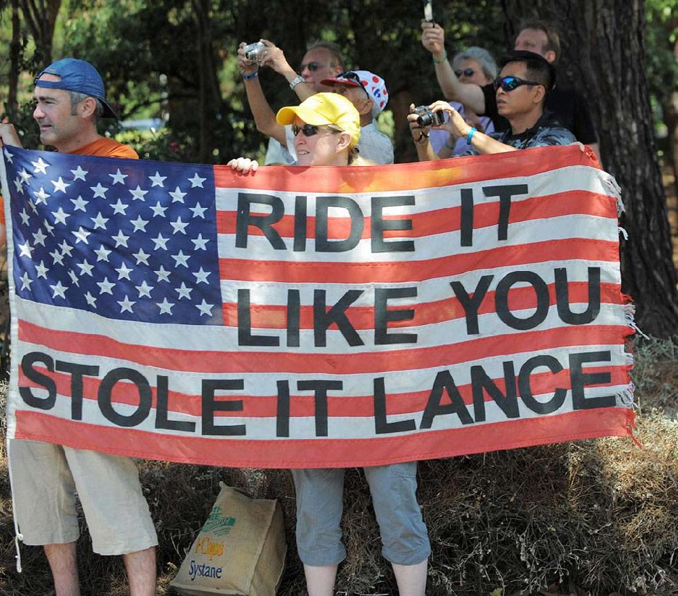11) Ожидающие велогонщиков на пятом круге гонки 8 июля фанаты, держат флаг, надпись на котором обращена к семикратному победителю Тура де Франс Лэнсу Армстронгу. (Patrick Hertzog/AFP /Getty Images)