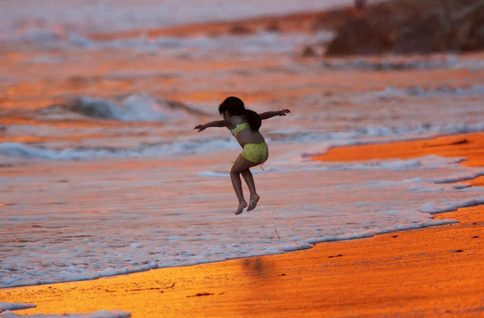 5. Ребенок играет в прибое, волны которого покраснели, отражая дым от пожара Иесусита на пляже Баттерфляй 7 мая в Монтесито, к югу от Санта-Барбары, Калифорния. (David McNew, Getty Images)
