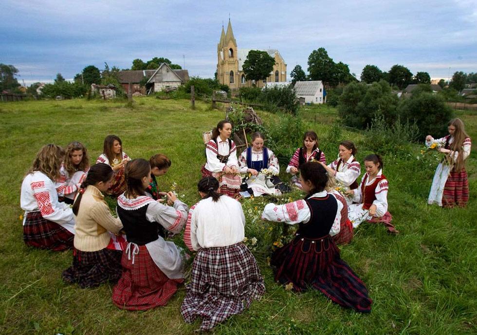 16) Белорусские женщины плетут венки во время празднования дня Ивана Купала неподалеку от города Раков 6 июля. Этот праздник знаменует день летнего солнцестояния. (Vasily Fedosenko/Reuters)