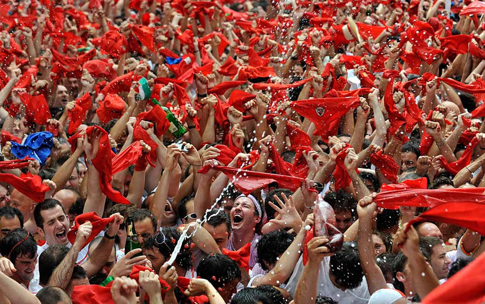 17) Люди держат традиционные красные платки в день начала фестиваля в честь святого Фермина в Памплоне, Испания, 6 июля. Этот фестиваль, особенно известный своими гонками с быками, начался сегодня традиционным запуском ракеты и продлится до 14 июля. (Eloy Alonso/Reuters)