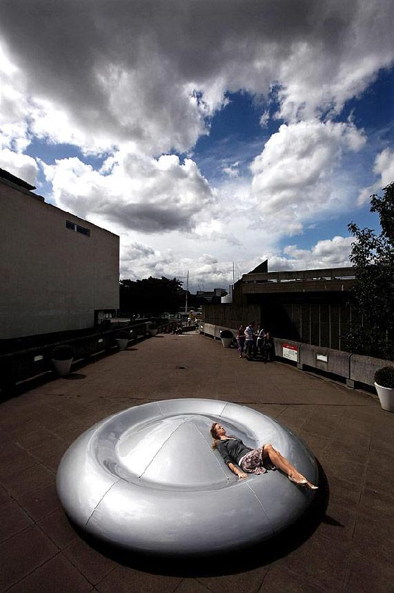 18) Девушка лежит на новой «скамейке» от художника Питера Ньюмана в Лондоне 6 июля. Скульптура, названная «Небесная станция» находится за пределами галереи Хэйвуд и открыта для общественности до 14 сентября. (Dan Kitwood/Getty Images)
