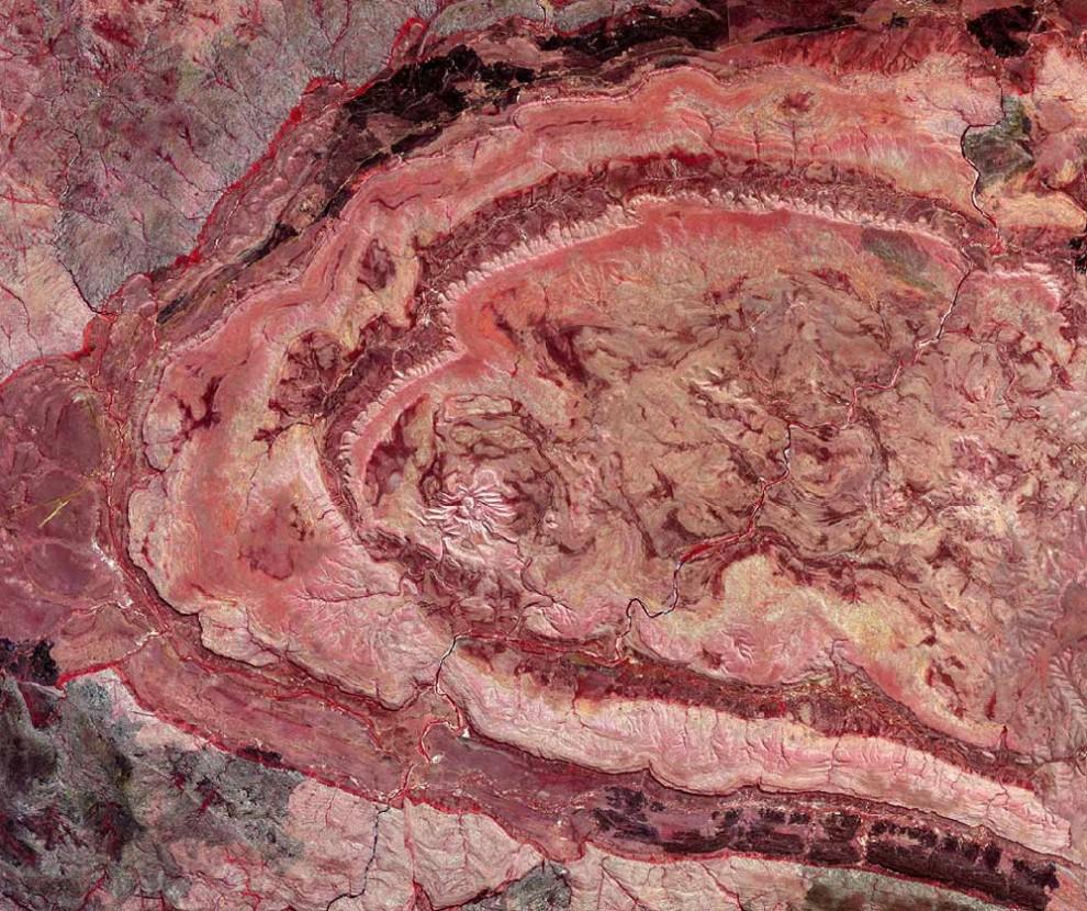 6. Как оценивают некоторые ученые, каждую 1000 лет с Землей сталкивается большой астероид или комета. Под «большим» они понимают астероид с силой удара, равным 10 мегатонн бомбы. Наверху: на этом снимке со спутника, представленном в искаженном цвете, показан кратер Спайдер в Австралии. Ученые полагают, что это – последствия метеора, который упал на Землю 600-900 миллионов лет назад. (US / Japan ASTER Science Team / NASA).