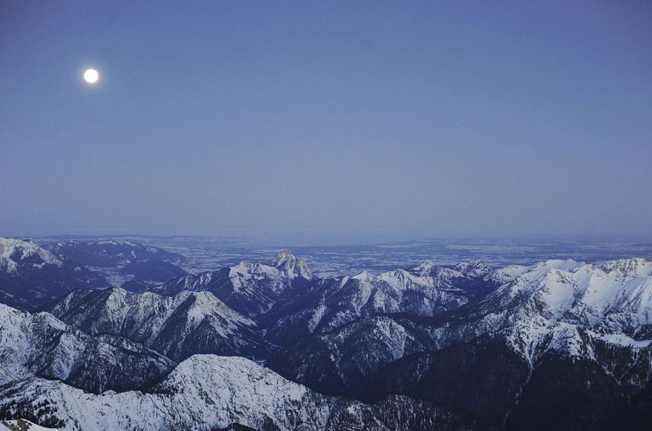 6) На этом снимке полная луна зависла над альпийской панорамой на пике Зугшпиц, Германия, как раз перед рассветом 11 января 2009 года. Перед самым рассветом альпинист-любитель отправился по канатной дороге на самую высокую точку в Германии на пронизывающем холоде. (Oliver Lang, AFP/Getty Images)