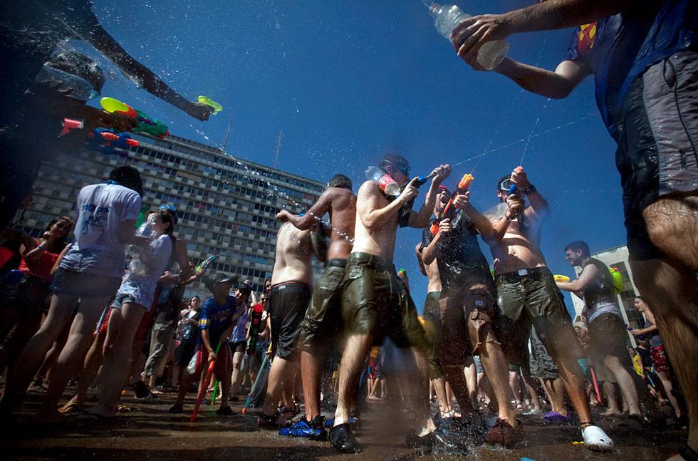 30) Израильтяне брызгаются водой во время ежегодной водяной битвы на площади Рабин в Тель-Авиве 3 июля. (Oded Balilty/AP)