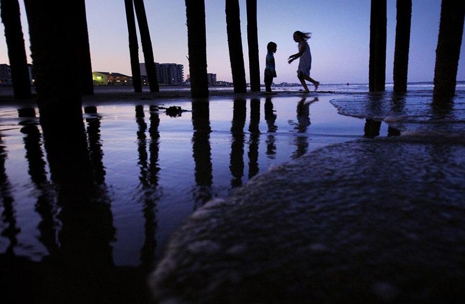 7. 3-летний Джослин Тэйблман и 10-летняя Эбби Донован – оба из города Сакко, штат Мэн,– играют под пирсом в сумерках 9 июля на пляже Олд Очард, Мэн. (Robert F. Bukaty, AP)
