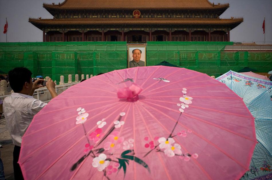 7. Туристы под зонтиками проходят мимо Ворот Тяньаньмэнь, окруженных строительными лесами и зеленой сеткой из-за реконструкции, проводимой к 60-ой годовщине основания Китайской Народной республики в Пекине, Китай, 14 августа. (Alexander F. Yuan, AP)