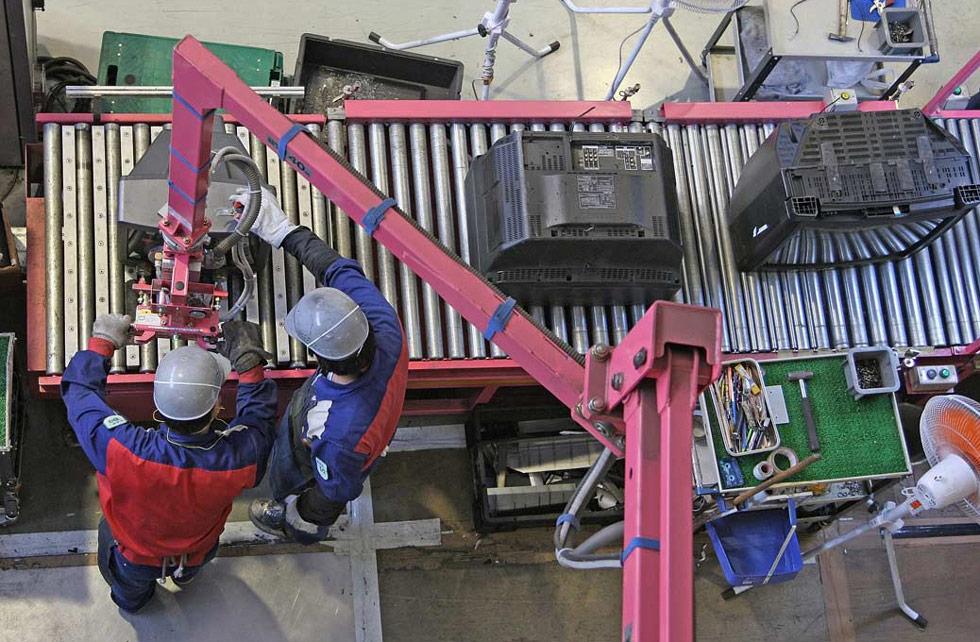 35) Рабочие помещают телевизор на конвейер во время процесса переработки в центре компании Panasonic Eco Technology в Японии 2 июля. В этом центре ежегодно разбирается около 700 000 телевизоров, кондиционеров, стиральных машин и холодильников, и 90% этих продуктов перерабатывается. (Junko Kimura/Getty Images)