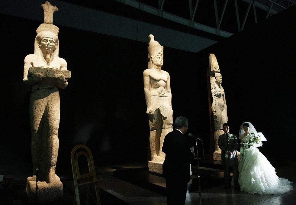 36) Юрико Касуя и Юния Курамото венчаются перед египетскими статуями возрастом 2000 лет в Японии 1 июля. Эти три статуи изображают Хапи – бога реки Нил - фараона и королеву. Выставка «Затонувшие сокровища Египта» включает в себя 489 экземпляров, поднятых со дна Средиземного моря в Александрии. Молодожены получили восьмидневный медовый месяц в Египте. (Junko Kimura/Getty Images)