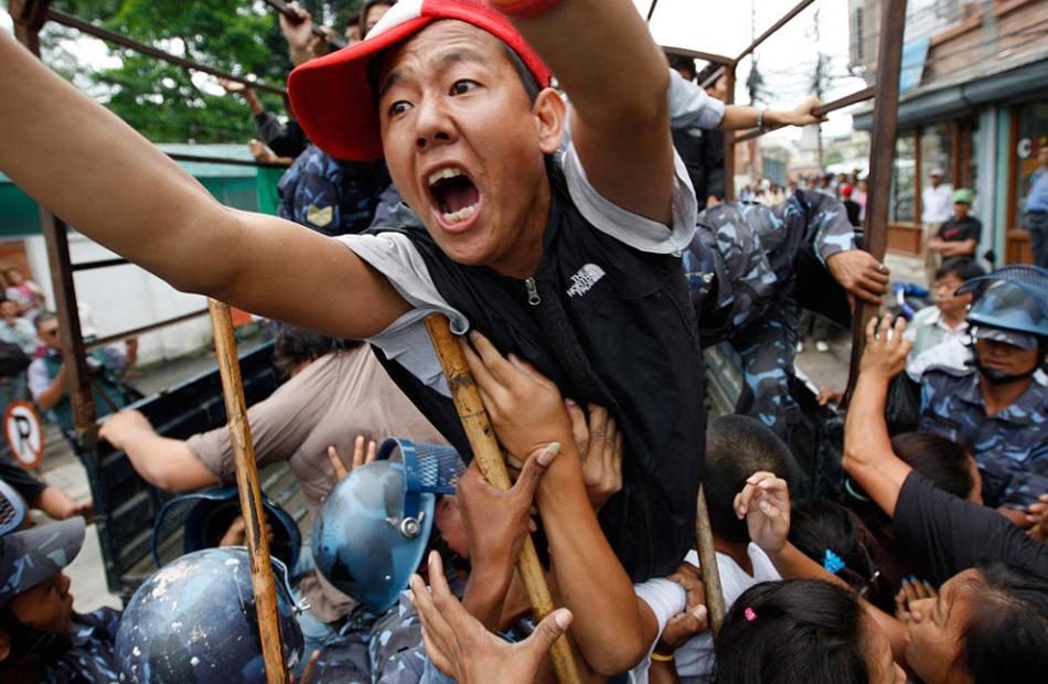 8. Тибетские эмигранты выкрикивают лозунги против китайского правительства во время акции протеста у входа в офис Объединенных Наций в Катманду, Непал, 15 августа. Группа тибетцев приняла участие в демонстрации, целью которой было привлечь внимание ООН к несоблюдению китайским правительством прав человека в Тибете. (Gemunu Amarasinghe, AP)