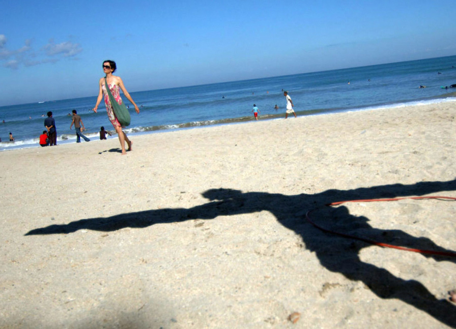 10) Тень туриста, несущего доску для серфинга на пляже Кута, в то время как другие туристы наслаждаются солнцем, пока жители острова голосуют в центре на острове Бали в июле 2009 года. Индонезия провела свои вторые президентские выборы с момента падения диктаторства Сухарто, и бывший генерал Сусило Бамбанг Юдхойоно был выбран на второй срок.