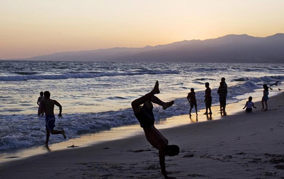 9. Люди плавают в Тихом океане и играют на пляже у пирса Санта Моника в одноименном городе, штат Калифорния, 28 июля. (Philip Scott Andrews, AP)