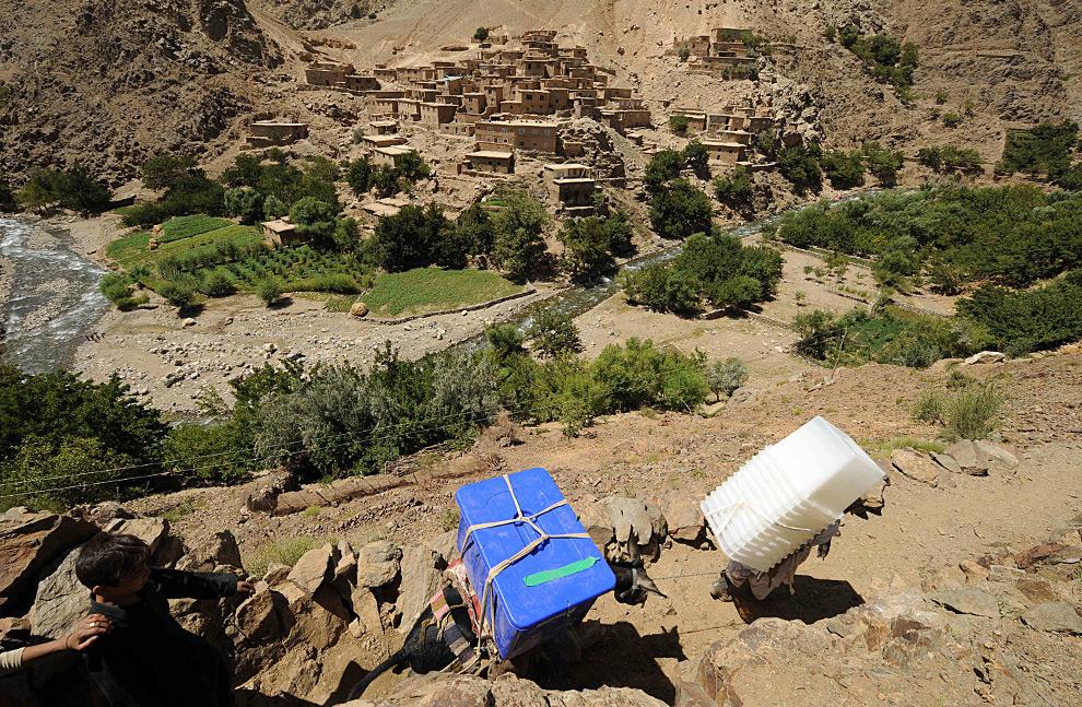 1. Афганец несет ящики для бюллетеней, и ведет за собой осла, нагруженного материалами для голосования, в скалистых горах долины Панджшер 19 августа 2009 года. (SHAH MARAI/AFP/Getty Images)