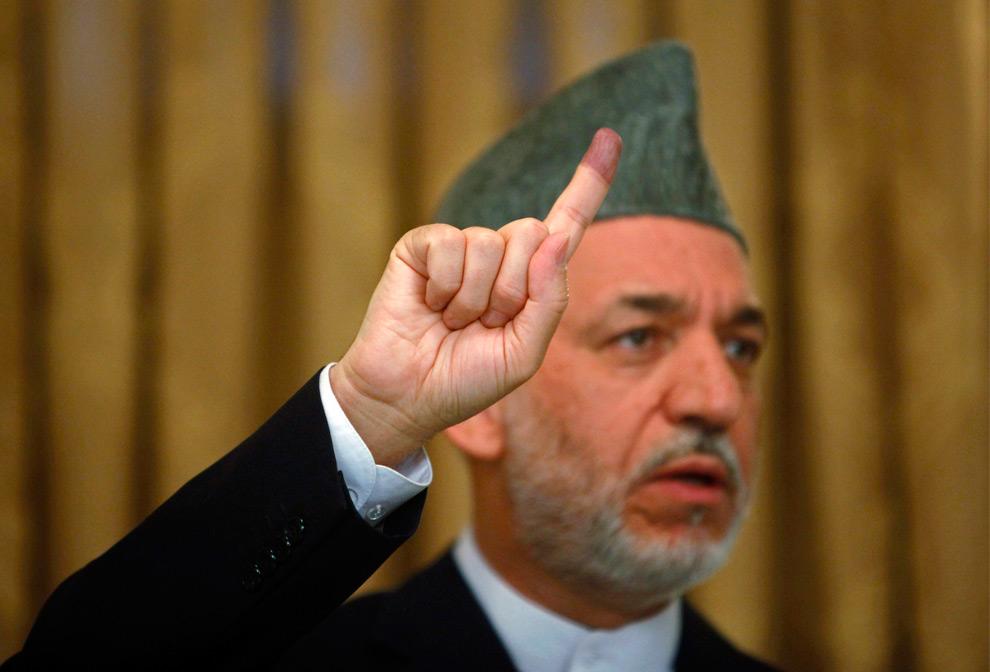 2. Пока еще действующий президент Афганистана Хамид Карзай поднимает помеченный чернилами палец во время пресс-конференции в день выборов в Кабуле 20 августа 2009 года. Миллионы афганцев пошли на выборы в четверг, несмотря на угрозы организации «Талибан» и внезапные атаки по всей стране. (REUTERS/Ahmad Masood)