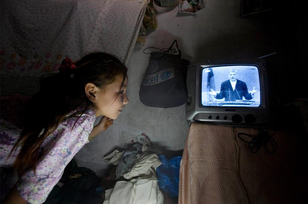 9. Девочка смотрит по телевизору выступление кандидата и нынешнего президента Хамида Карзая во время дебатов, транслировавшихся в прямом эфире, в Кабуле, в воскресенье 16 августа 2009 года. (AP Photo/Farzana Wahidy)