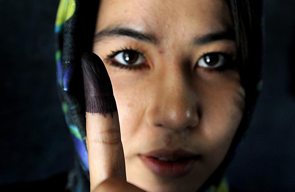 3. Афганская женщина показывает свой палец, помеченный несмываемыми чернилами, после того, как опустила свой бюллетень на избирательном участке в Кабуле 20 августа 2009 года. Афганский народ выбирал президента всего во второй раз за свою историю, отмеченную бесконечными войнами. В стране были приняты самые жесткие меры, чтобы предотвратить атаки организации «Талибан», угрожавшей проведению выборов. (SHAH MARAI/AFP/Getty Images)