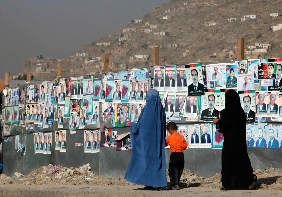 10. Афганские женщины и ребенок проходят мимо стены с фотографиями кандидатов в президенты и на посты местных органов управления в Кабуле 18 августа 2009 года. (REUTERS/Ahmad Masood)