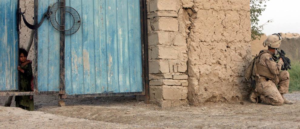 11. Ребенок выглядывает из ворот, в то время как американский пехотинец стоит на страже в Хан Нешине, провинция Гильменд, южная точка союзных войск, недалеко от границы с Пакистаном во вторник 25 августа 2009 года. (AP Photo/Lewis Whyld/PA Wire)