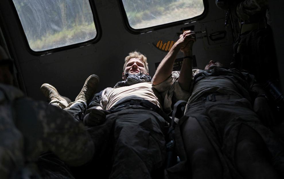 13. 19-летний солдат Кен Дайкс из Гринвиля, Теннеси, держит за руку другого солдата; оба ранены и лежат в санитарном вертолете после того, как их бронетранспортер наехал на мину в долине Танги афганской провинции Вардак 19 августа 2009 года. Солдаты служат во втором батальоне 87-ого пехотного подразделения третьей боевой бригады 10-го горного дивизиона. Один из солдат – 21-летний Джастин Р. Пелерин (нет на снимке) – был убит во время атаки. (AP Photo/David Goldman)
