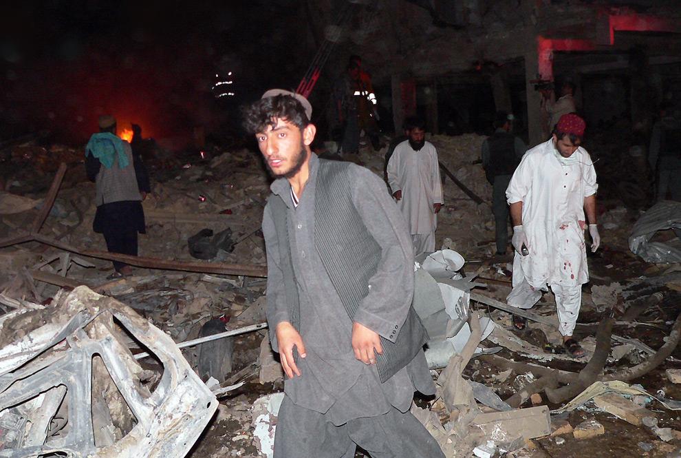 16. Афганцы на месте взрыва бомбы в городе Кандагар 25 августа 2009 года. Бомба взорвалась в деловом центре города, убив 36 человек и нанеся ранения всем, кто находился вблизи отелей и государственных офисов. Мощный взрыв бомбы, которая находилась в багажнике, вызвал обрушение 10 жилых домов. Спасатели пытались вытащить жителей из-под обломков под покровом ночи. (HAMED ZALMY/AFP/Getty Images)