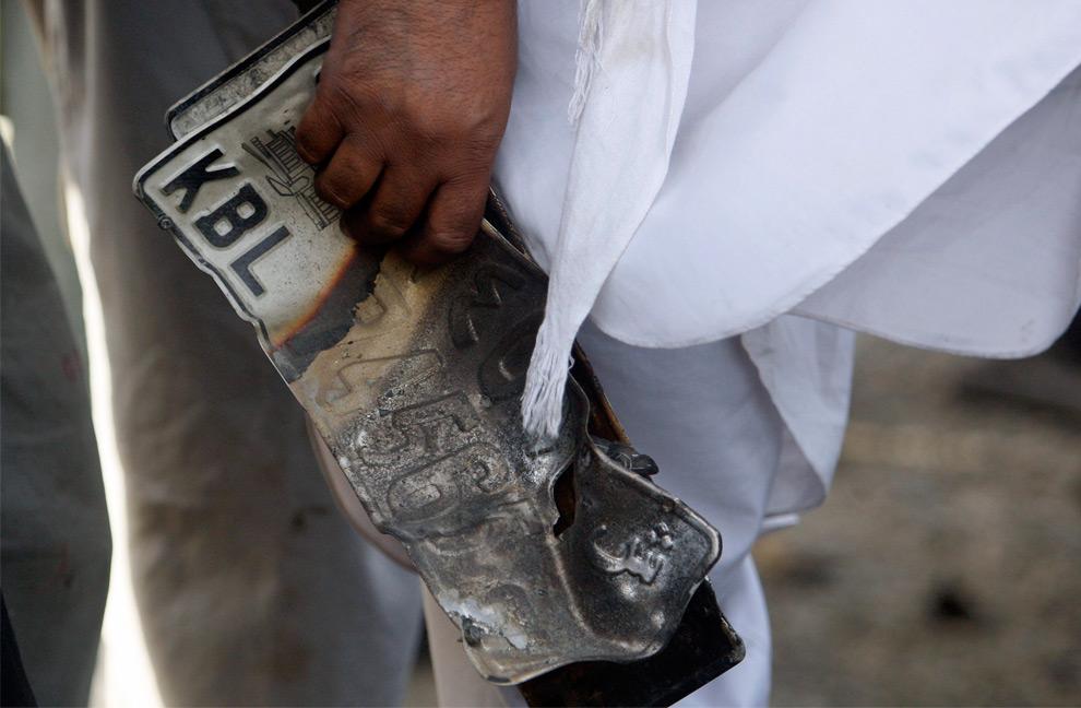 17. Мужчина держит номерной знак автомобиля на месте взрыва в Кабуле 18 августа 2009 года. 7 человек погибли и 52 получили ранения после того, как террорист-смертник направил свой автомобиль прямо в конвой западных бойцов в столице Афганистана во вторник – заявил Фарид Раед, официальный представитель министерства здравоохранения.  (REUTERS/Lucy Nicholson)