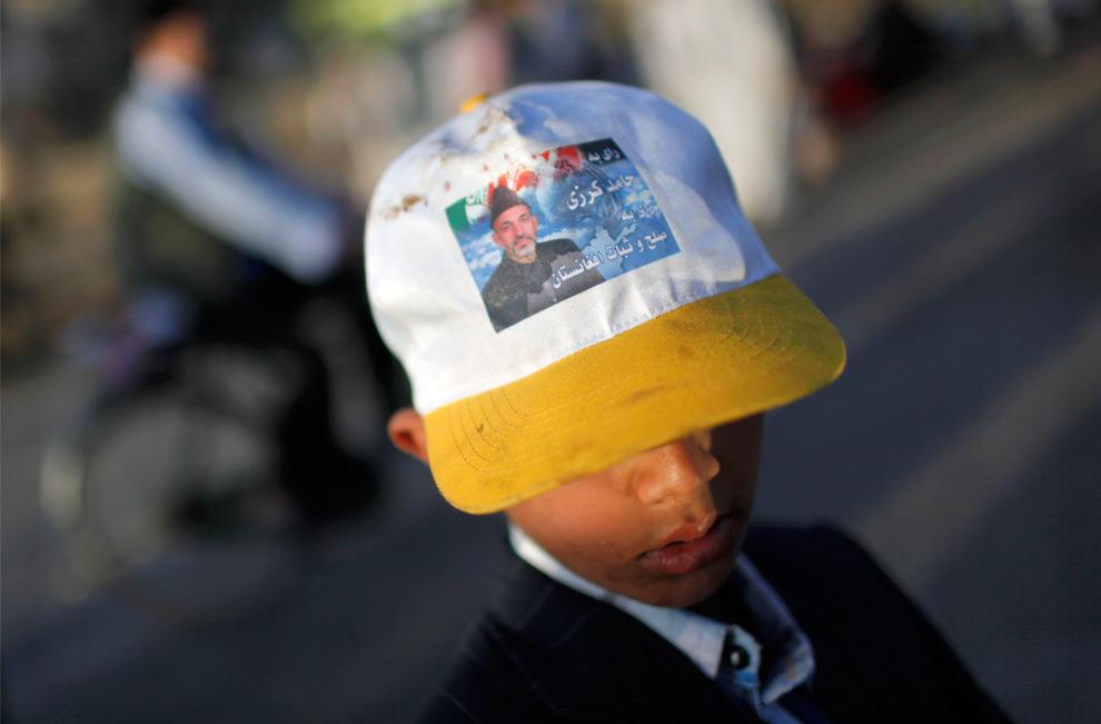 21. Афганский мальчик в кепке с фотографией кандидата в президенты и действующего президента Хамида Канзай в Кабуле в пятницу 21 августа 2009 года. (AP Photo/Kevin Frayer)