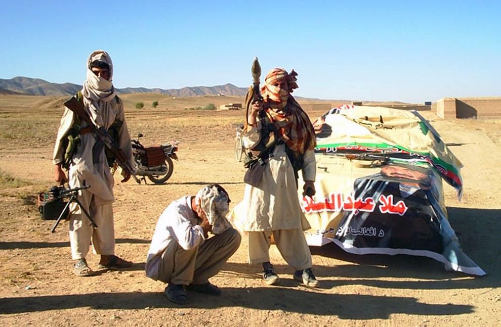 26. Боевики «Талибана» позируют со своим оружием, задержав человека за поддержку кандидата в президенты Муллаха Абдула Салама Рокети в неизвестной местности в Афганистане 19 августа 2009 года. (REUTERS/Stringer)