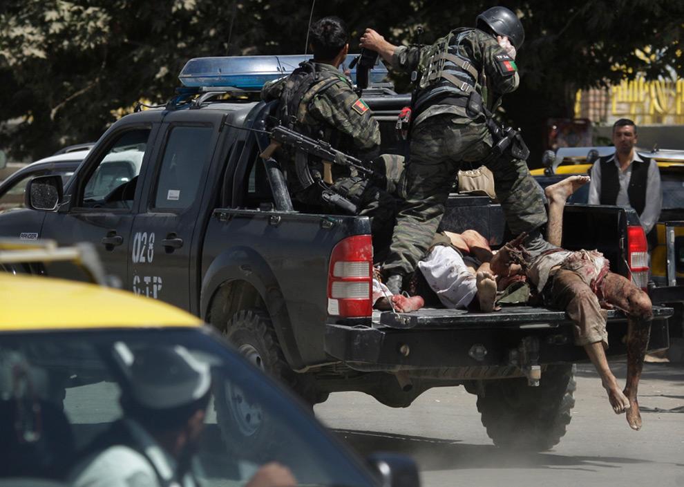 27. Афганская полиция везет в грузовике тела трех подозреваемых боевиков, убитых в перестрелке в Кабуле в среду 19 августа 2009 года. Перестрелки и взрывы взбудоражили столицу Афганистана в среду, накануне президентских выборов после того, как три боевика с автоматами Калашникова и ручными гранатами вбежали в банк. Полиция взяла здание штурмом и убила трех боевиков, заявило правительство страны. (AP Photo/Kevin Frayer)
