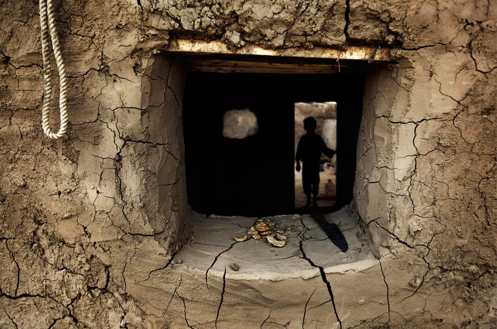 28. Мальчик входит в дом во временном лагере для пострадавших от взрыва в провинции Гильменд на окраине Кабула, во вторник 25 августа 2009 года. (AP Photo/Dima Gavrysh)