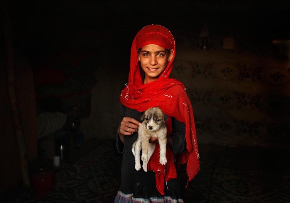 36. Девочка с щенком в бедном районе Теппе Мараньян в понедельник 24 августа 2009 года. (AP Photo/Dima Gavrysh)