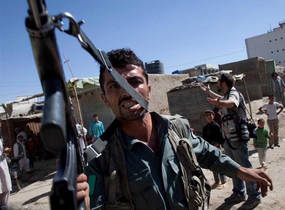 42. Офицер Афганской Национальной полиции угрожает фотографу своим автоматом, пытаясь защитить территорию банка, атакованного вооруженными боевиками 19 августа 2009 года в Кабуле, Афганистан. (Paula Bronstein/Getty Images)