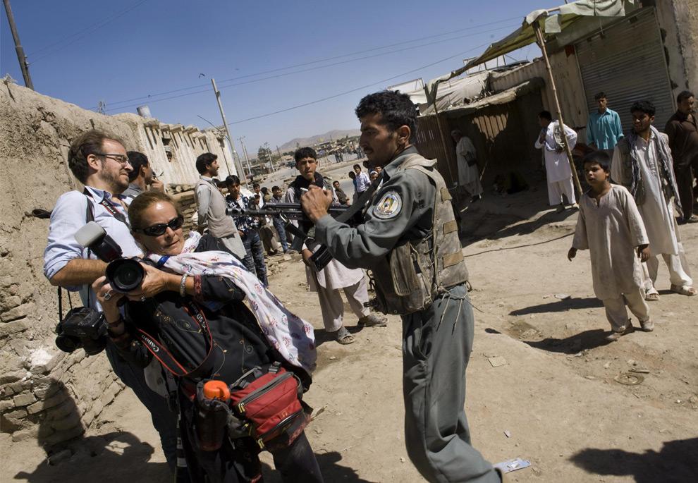 43. (Предыдущая фотография с другого ракурса): афганский полицейский поднимает оружие на фотожурналистов Полу Бронштайн и Кевина Фраера, не подпуская их к месту, где три вооруженных боевика захватили банк в Кабуле 19 августа 2009 года. (PEDRO UGARTE/AFP/Getty Images)