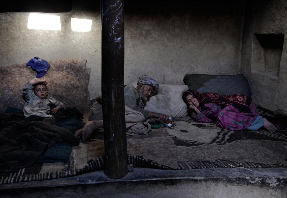 1. Житель деревни Сараб, опийный наркоман Ислам Бег (в центре) нагревает несколько грамм опиума во время утренней «процедуры» курения. Снимок сделан в провинции Бадахшан в Афганистане 13 июля. «У меня нет жизни. У меня вообще ничего нет. Все потрачено на опиум», - говорит Бег, чья родные также являются наркоманами. (AP/Julie Jacobson)