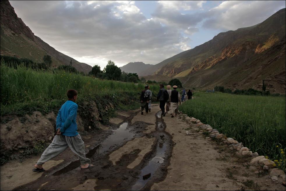 3. Жители деревни Сараб идут по грязной дорожке из одной части деревни в другую. Снимок сделан в афганской провинции Бадахшан, 12 июля. Расположение на высоте 2,5 кмнад уровнем моря, а также тот факт, что это последняя деревня вверх по речной долине, делают путешествие по грязным дорогам к докторам довольно затрудненным. «Опиум – наш доктор», - говорит житель деревни, использующий опиум для облегчения боли. (AP/Julie Jacobson)