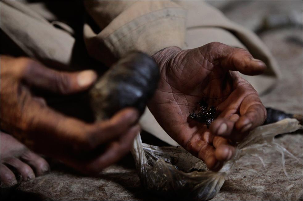 6. Житель деревни Сараб, опийный наркоман Ислам Бег убирает остатки опиума после утреннего курения. (AP/Julie Jacobson)
