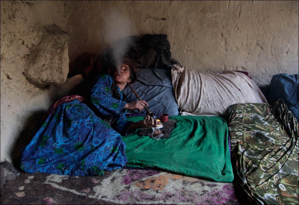 7. Жительница деревни Сараб, наркоманка Ян Бегум курит опиум. «Курение помогает от моей астмы», - говорит Бегум, у которой нет ни денег, ни транспорта, чтобы поехать к доктору. (AP/Julie Jacobson)