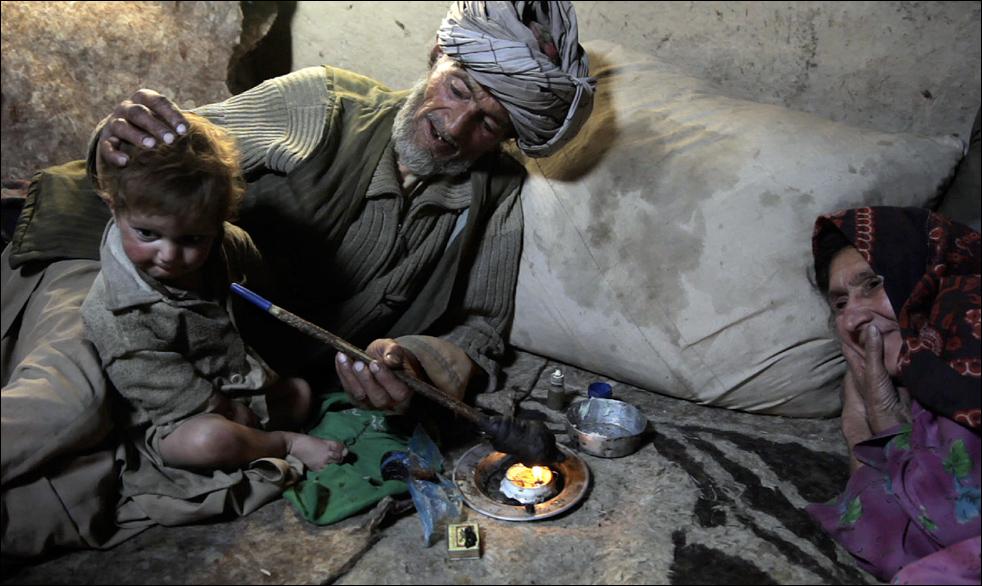 9. Житель деревни Сараб, опийный наркоман Ислам Бег (в центре) предлагает трубку с опиумом своему внуку во время утреннего курения. (AP/Julie Jacobson)