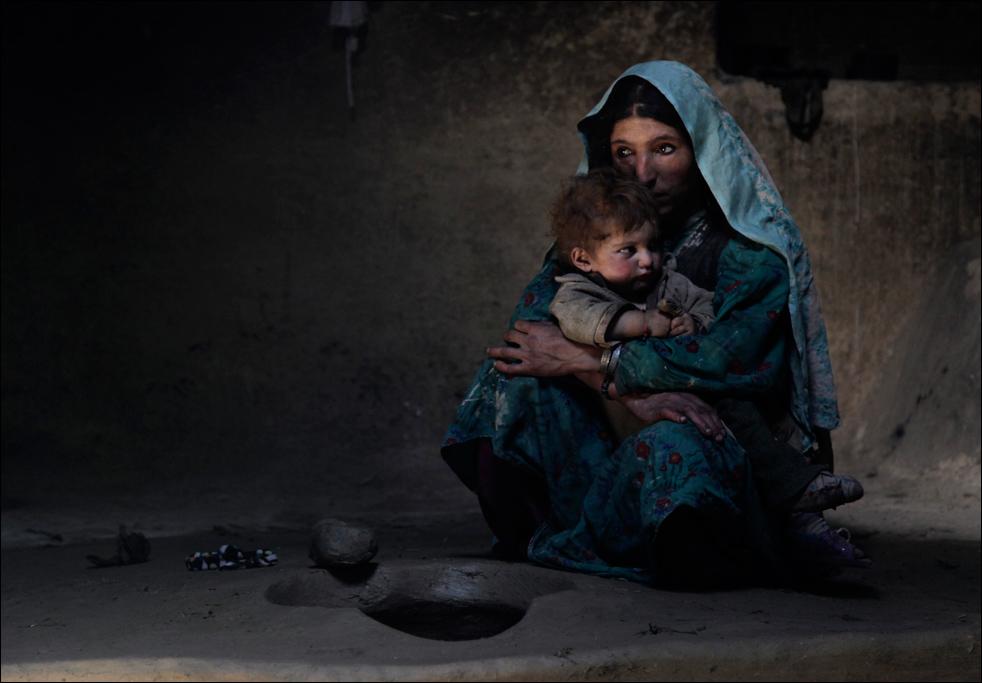 10. Жительница деревни Сараб Раихан успокаивает годовалого сына после утренней церемонии курения опиума с остальными членами семьи в афганской провинции Бадахшан. Раихан пристрастилась к опиуму во время беременности, сделав сына наркоманом с рождения. «Когда он родился, он плакал днями и ночами. Но когда она дует на него дымом от опиума, он засыпает», - говорит отец Раихан Ислам Бег. (AP/Julie Jacobson)