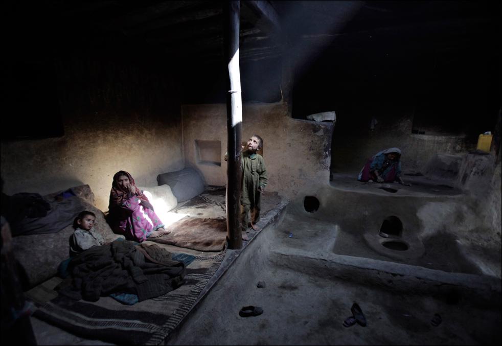 12. Жительница деревни Сараб, Раихан (справа) чистит печь, пока ее мать и дети наблюдают за ней после утреннего курения опиума всей семьей. «Я не завтракала. Я могу смириться с голодом, но без опиума я не могу», - говорит Раихан. (AP/Julie Jacobson)